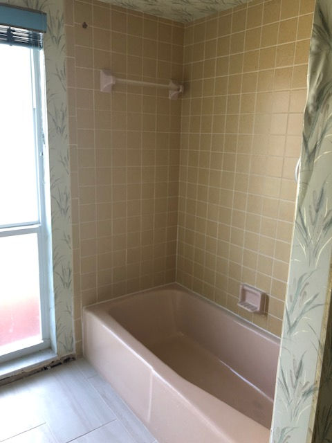 Pink tub with yellow tile walls