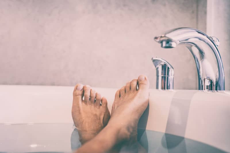 feet propped on the edge of reglazed bathtub